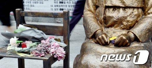 광복70주년이 하루 지난 16일 오후 서울 종로구 일본대사관 앞 평화의 소녀상에 꽃다발이 놓여 있다. /뉴스1 © News1