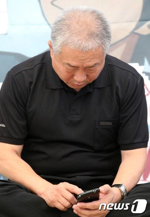 [사진]휴대폰 만지는 김동만 위원장