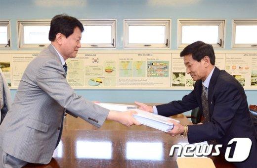 15일 판문점에서 남북 연락사무소의 연락관들이 10월 개최 예정인 남북 이산가족상봉을 위한 생사확인 의뢰서를 교환하고 있다. (통일부 제공) 2015.9.15/뉴스1 © News1 조희연 기자