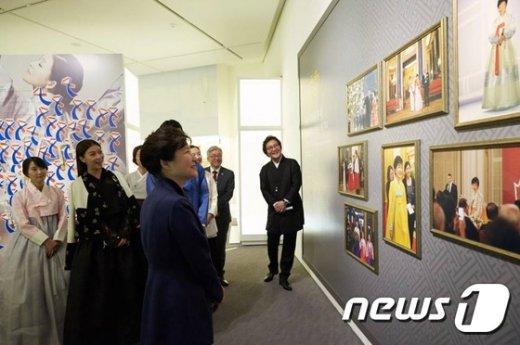 [사진]외국순방 중 입은 한복 보는 박근혜 대통령