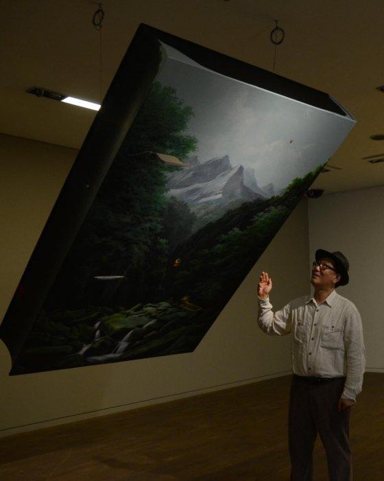 """유선태 작가가 가나아트센터 내에 설치된 자신의 풍경화 작품 앞에서 설명을 하고 있다. 유 작가는 """"내게 풍경은 과거이자 현재이고 미래""""라고 말했다. /사진제공=가나아트센터"""