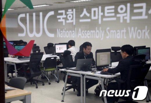 서울 여의도 국회에 마련된 스마트워크센터에서 관계 공무원들이 컴퓨터, 복사기 등을 이용하고 있다. 스마트워크센터는 국회에 마련된 정부세종청사 공무원들의 원격근무용 사무실로 118제곱미터에 30여 석 규모로 설치됐다. 2013.4.8/뉴스1