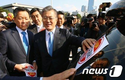 [사진]차량에 국정교과서 반대 스티커 붙이는 문재인 대표