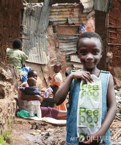 세계 3대 슬럼가로 꼽히는 아프키라 케냐 나이로비 키베라에서 한 소녀가 '피푸백'을 들고 서있다/출처=peepoople