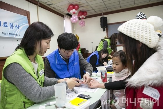 KIC 직원들이 13일 '다문화가정 및 외국인 근로자' 의료봉사에서 외국인 근로자의 의료검진을 돕고 있다. /사진제공=KIC.