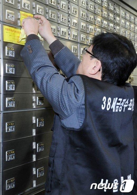 서울시 38세금징수과 직원들이 서울의 한 은행에서 1000만원 이상 세금 체납자에 대한 대여금고 봉인 작업을 하고 있다. /뉴스1 @news1