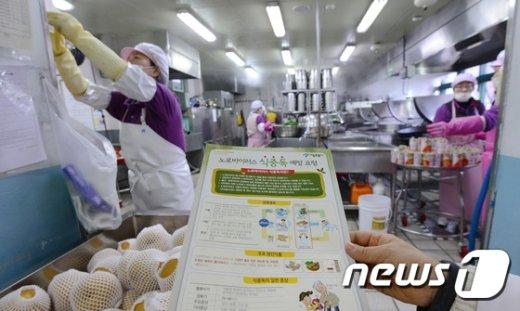 서울 강북구 한 초등학교 급식실에서 영양사가 식중독 예방요령 안내문을 들고 있다./뉴스1 © News1 박지혜 기자