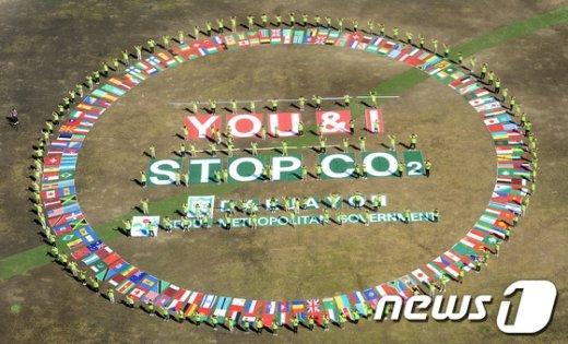 대학생 환경단체 대자연 회원들이 서울시와 공동으로 2일 오전 서울광장에서 기후변화 방지를 위해 즉시 행동에 나설 것을 촉구하는 메시지 '너와 나 모두가 온실가스 배출을 멈춰야 한다(YOU & I Stop CO2)'를 만국기 안에 표현하는 퍼포먼스를 펼치고 있다.  2013.9.2/뉴스1