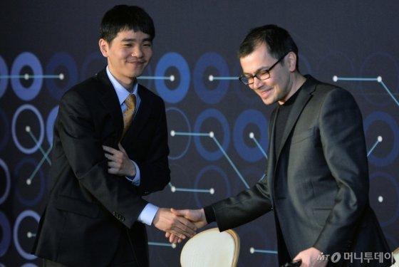 이세돌 9단이 15일 서울 종로구 포시즌스 호텔에서 열린 '구글 딥마인드 챌린지 매치' 인공지능(AI) 바둑 프로그램 알파고(AlphaGo)와의 5번기 제5국 기자회견을 마치고 데미스 하사비스 구글 딥마인드 대표와 악수를 하고 있다. 이세돌 9단은 이날 대국에서 끝내기 승부에 돌입했지만 280수 만에 패했다. 2016.3.15/뉴스1