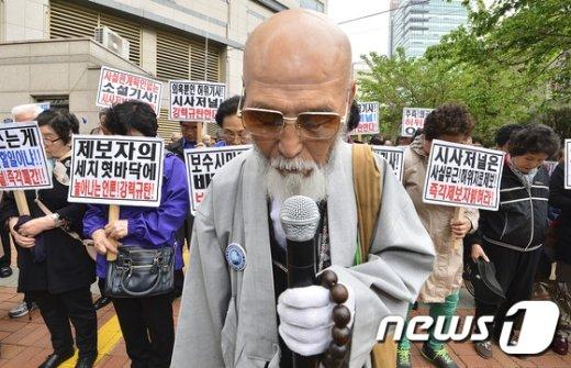 어버이연합 회원들이 21일 오후 서울 용산구 시사저널 앞에서 시사저널 규탄 기자회견을 열고 국민의례를 하고 있다.//뉴스1 © News1 신웅수 기자