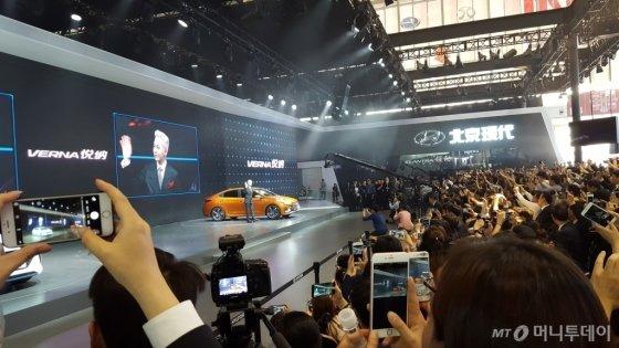 25일 베이징모터쇼 프레스데이 행사에 현대자동차 베르나 홍보모델 지드레곤이 등장하자 취재진이 일제히 손을 들어 사진을 찍고 있다. /사진=양영권 기자