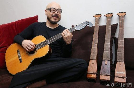 기타리스트 이병우가 새 음반에서 쓰인 기법을 마틴 사가 초기 제품을 특별히 제작한 기타로 선보이고 있다. 그는 &quot;그간 풀리지 않은 숙제를 다 푼 것 같은 기분&quot;이라고 웃었다. 오른쪽 통이 없는 기타들은 이병우가 직접 제작한 제품이다. /사진=이동훈 기자<br />