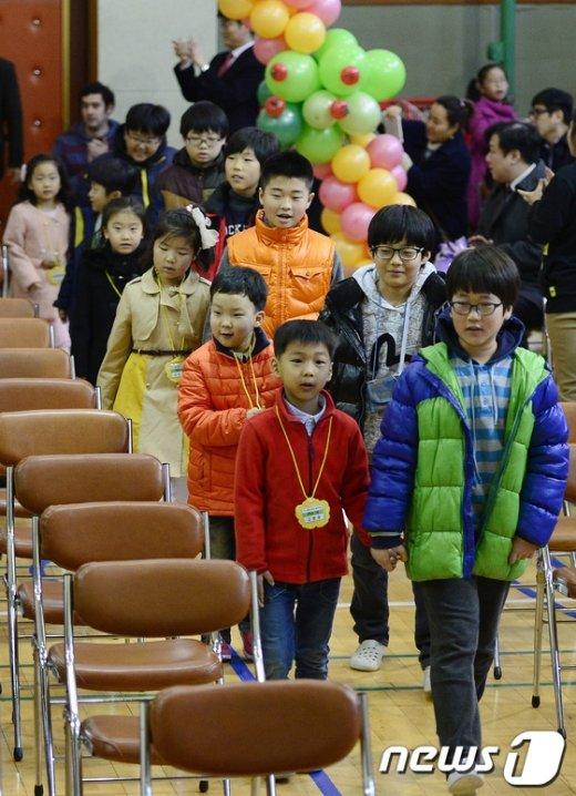서울 종로구 교동초등학교에서 열린 입학식에 1학년 신입생들이 6학년 선배들의 손을 잡고 입장하고 있다. /뉴스1 © News1
