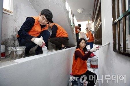 한화 임직원들이 차상위계층 주거환경개선을 위해 페인트칠을 하고 있다 /=한화