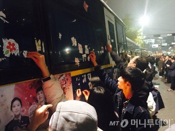 19일 밤 서울 종로구 내자동 로터리 인근에 설치된 차벽에 붙은 스티커를 시민들이 촛불집회가 끝나가자 자발적으로 제거하고 있다. /사진=김평화 기자