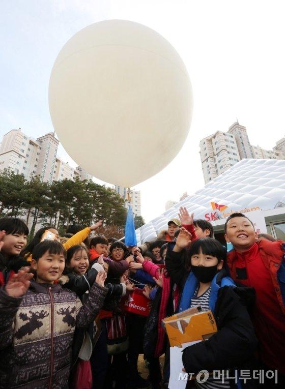 각리초등학교 학생들이 운동장에서 '우주 풍선 날리기'에 참여하고 있는 모습. /사진제공= SK텔레콤