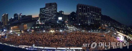 박근혜 대통령 탄핵소추안이 가결된 다음 날인 10일 광화문 광장에 모인  시민이 촛불을 밝히고 '박근혜 대통령 즉각 퇴진' 구호를 외치고 있다. <사진공동취재단>