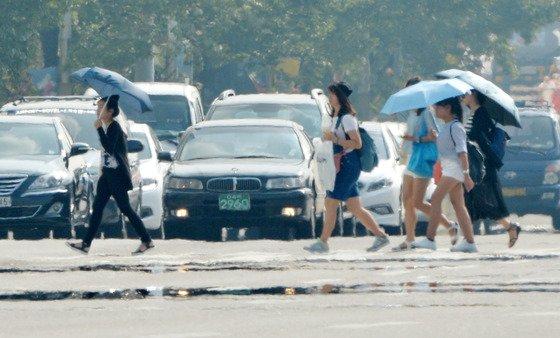 전국적으로 폭염특보가 내린 지난 8월12일 오후 아지랑이가 피어 오르는 서울 여의도공원 앞 횡단보도에서 양산을 쓴 시민들이 발걸음을 재촉하고 있다. /사진=뉴스1