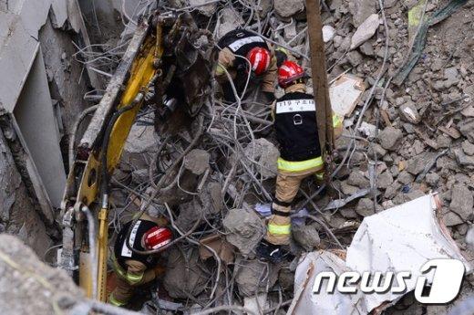 전날 철거공사 중 건물이 무너져 인부 2명이 매몰된 서울 종로구 낙원동 사고 현장에서 8일 오후 소방대원들이 매몰된 인부 조모씨(48세) 의구조작업을 벌이고 있다.  2017.1.8/뉴스1 © News1 박세연 기자