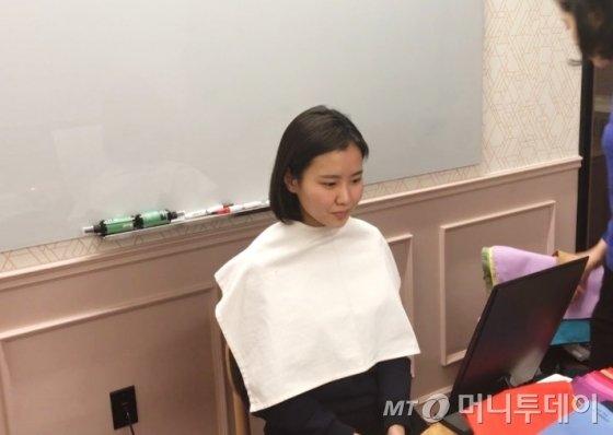 진단을 시작하기 전 흰색 케이프를 착용한 모습. / 사진=한지연 기자