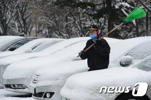 일년 중에 가장 춥다는 대한(大寒)이자 전국에 많은 눈이 내리는 20일 오전 서울 강남구 대치동 한 아파트에서 경비원이 자동차에 쌓인 눈을 치우고 있다. 2017.1.20/뉴스1 © News1 임세영 기자