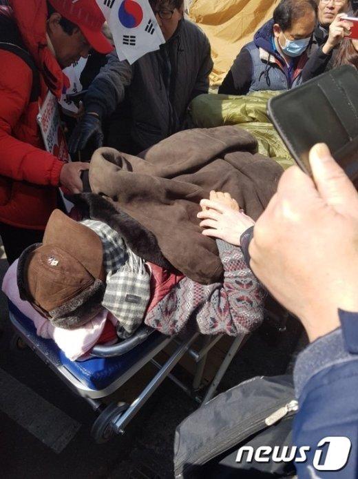 권영해 탄기국 공동대표가 8일 오후 1시쯤 서울 종로구 헌법재판소 앞에서 구급차에 실려 이송되고 있다. 2017.3.8/뉴스1 © News1