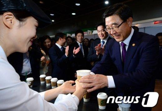 시간선택제 근로자로부터 커피를 건내 받고 있는 이기권 고용노동부 장관. © News1 박정호 기자