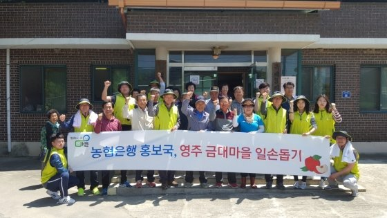 NH농협은행 홍보국 직원들이 19일 경북 영주 단산면 금대마을 마을회관에서 주민들과<br />  일손돕기 중 기념사진을 찍고 있다. / 사진제공=농협은행