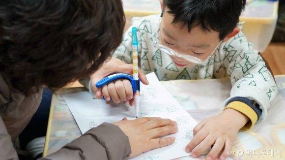 그립플레이가 제작한 보조기구에 펜을 꽂아 그림을 그리는 소년/사진제공=그립플레이