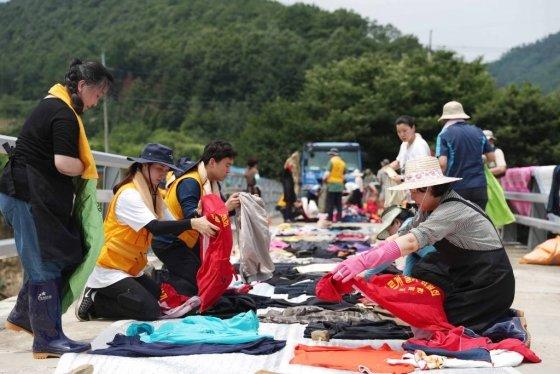 김정숙 여사가 침수 피해를 입어 세탁한 옷가지를 건조하기 위해 정리하고 있다. /사진=뉴시스
