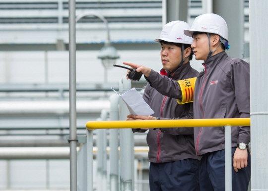 금호석유화학그룹 직원들이 작업장 안전을 위해 매뉴얼을 보며 설비를 체크하고 있다/사진제공=금호석유화학그룹