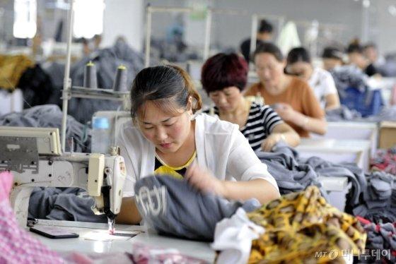 중국 산동성에 위치한 한 의류공장에서 직원들이 작업을 진행하고 있다. 미국이 중국에 통상 제재를 결정하면 미국으로 수출 비중이 큰 중국의 의류나 가전, 완구 등의 업종이 타격을 받을 것으로 예상된다. /AFPBBNews=뉴스1