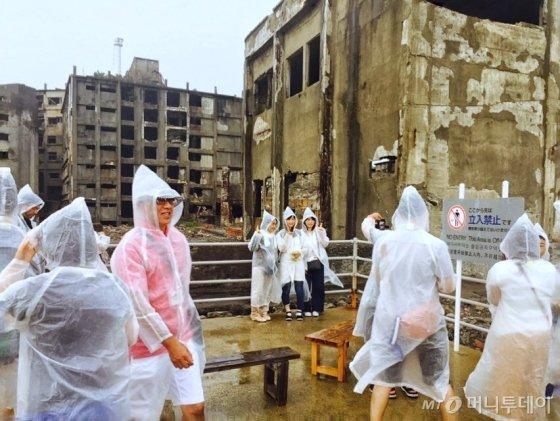 콘크리트 건물 잔해를 배경으로 기념 사진을 찍는 방문객들./사진=남궁민 기자