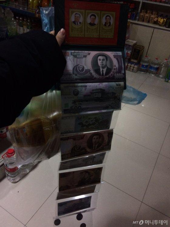 이씨가 기자에게 보여준 사진. 이씨는 중국 연길의 한 슈퍼마켓에서 팔고 있는 북한 화폐 모음집을 들고 찍었다. /사진=이재은 기자