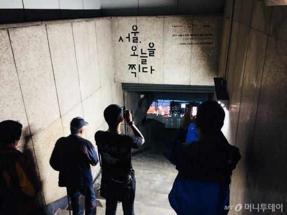 신설동 유령역 입구에서 사진을 찍는 관람객들 /사진=남궁민 기자