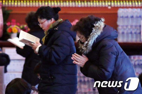 서울 종로구 조계사에서 수험생 학부모들이 자녀의 합격을 기원하며 간절한 마음으로 기도를 드리고 있다.  © News1 민경석 기자