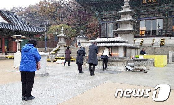 수능을 하루 앞둔 22일 수험생 학부모들이 서울 강남구 봉은사를 찾아 불탑 앞에서 합장하고 있다. © News1