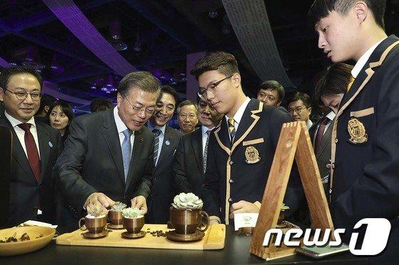 [사진]커피찌꺼기로 만든 친환경 화분 살펴보는 문 대통령