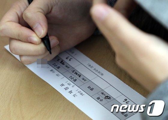 2018학년도 대학수학능력시험을 마친 고3수험생이 가채점표를 작성하고 있다. /뉴스1 © News1 김명섭 기자