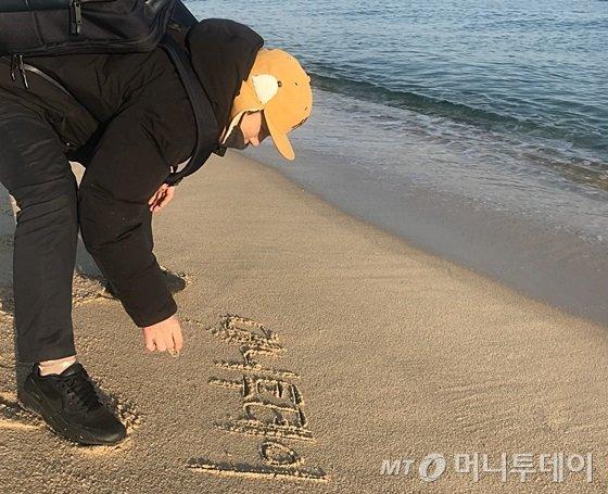 한 남성이 강릉 경포해수욕장 모래사장에 글 쓰고 있다. /사진=머니투데이