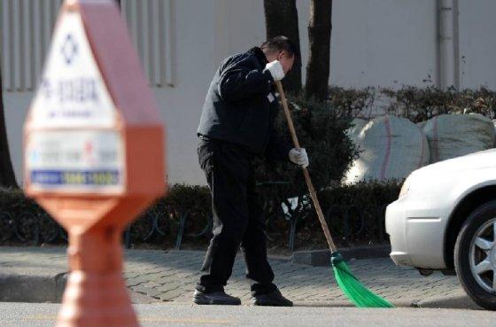 5일 서울 양천구의 한 아파트단지에서 한 경비원이 청소를 하고 있다./사진=뉴스1<br />