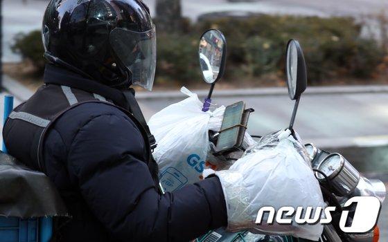 서울 중구 거리에서 퀵배달 기사가 방한장갑위에 비닐로 감싼 채 오토바이 운행을 하고 있다. (기사내용과 관계없음)  2018.1.23/뉴스1 © News1 김명섭 기자