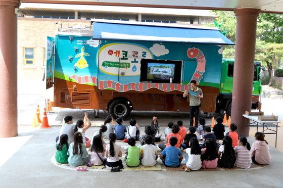 김윤원 코오롱 CSR사무국 차장이 경기도 시흥시 냉정초등학교 학생들에게 친환경 에너지 교육을 펼치고 있다. 그는 5톤 트럭을 개조한 '친환경 트랜스포머'를 타고 다니며 교육을 한다./사진제공=코오롱