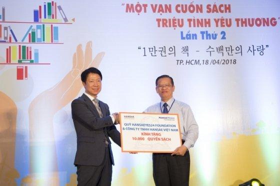 문양원 한세베트남총괄법인장(왼쪽)이 응웬 꾸앙 븬 호치민시 교육부 대표에게 도서기증증서를 전달하는 모습/사진제공=한세실업
