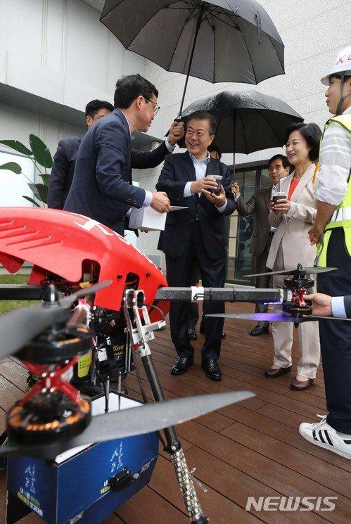 【서울=뉴시스】전신 기자 = 문재인 대통령이 17일 서울 마곡 R&D 단지에서 열린 혁신성장 점검회의에 앞서 사전환담 중 드론이 운반한 커피음료를 받고 있다. 2018.05.17.   photo1006@newsis.com