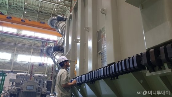 LS산전 부산사업장 관계자가 HVDC 변환용 변압기를 점검하고 있는 모습/사진=이정혁 기자