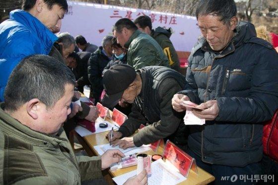 지난 1월 진행된 중국 허베이성 난위촌 농촌합작사의 배당금회의에서 마을 주민들에게 배당금이 지급되고 있다./사진제공=중국삼성