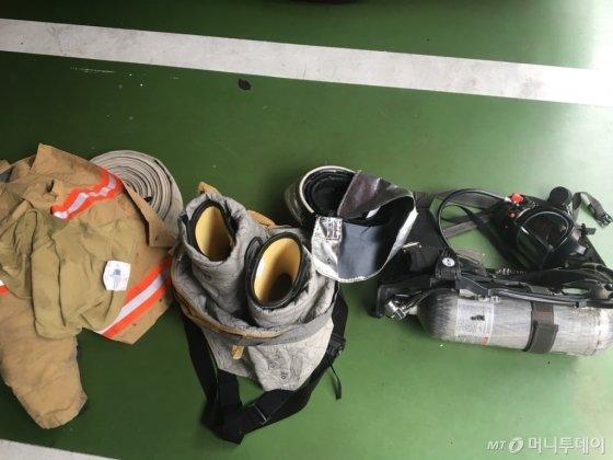 소방관들이 입는 방화복 장비 일체. (왼쪽부터) 두건, 방화복 상의, 방화복 하의와 신발, 압축산소통, 면체./사진=남형도 기자