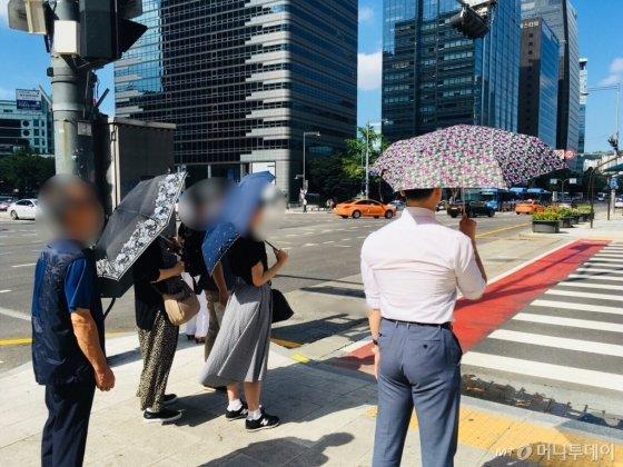 서울 광화문 한복판서 꽃무늬 양산(장모님 협찬)을 쓴 기자. 양산을 거의 처음 쓰는터라 요령이 부족해, 등쪽에 고스란히 햇빛을 받고 있다. 반면 양산을 뒤쪽까지 안정적으로 가리고 있는, '양산쓰기 만렙'인 왼쪽 행인들./사진=남궁민 기자