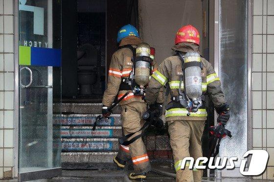 [사진]건물 내부 진입하는 소방대원들